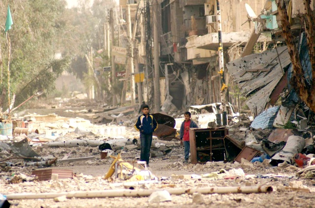 Boys walk along a damaged street filled with debris in Deir al-Zor