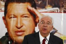 Venezuela's Energy Minister Rafael Ramirez talks to the media in front of a giant picture of Venezuela's President Hugo Chavez during a news conference at the headquarters of the state-run oil company PDVSA in Caracas