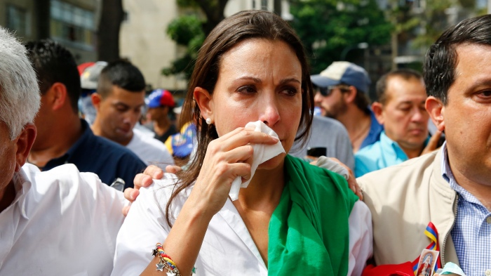 Venezuelas opposition leader Corina Machado reacts after inhaling tear gas after she tried to take a seat at the national assembly in Caracas