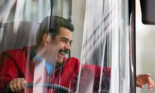 Venezuela's President Maduro drives the 'homeland bus' while he leaves the airport in Caracas after arriving back to the country